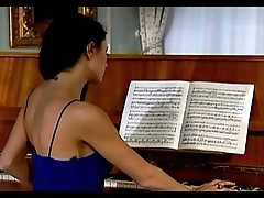 Sofia Cuci playing piano while couple is shagging on sofa