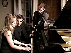 Blonde virago playing piano and two cocks